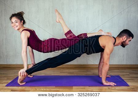 Beautiful Woman With Curly Hair And A Muscular Man Practicing Yoga Together On The Yoga Mat . Concep