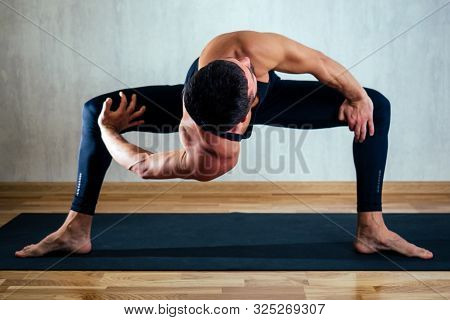 A Man In Dark Sportswear Practicing Yoga On A Dark Background. Asana On The Floor On Yoga Mats. The