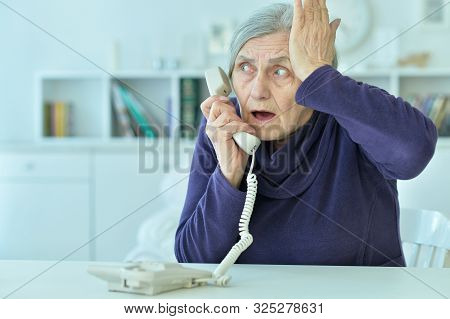 Portrait Of Sad Senior Woman Talking On Phone