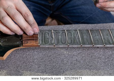 The Master Removes Masking Tape With Paste From The Guitar Neck After Polishing Frets.