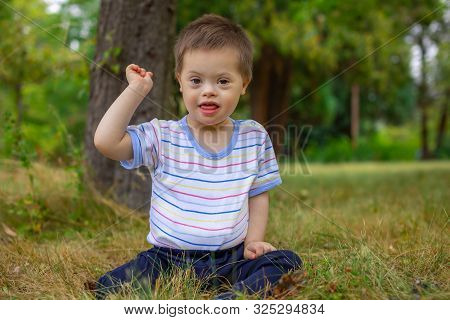 Portrait Of Cute Small Boy With Down Syndrome, Child Playing In Summer Day On Nature