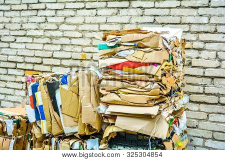 Bundle Of Wastepaper Cardboard To Be Recycled. Paper Cardboard Is Bundled Into Bale. Scene Is Outdoo