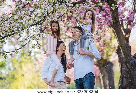 Young Parents With Small Daugthers Standing Outside In Spring Nature.