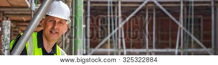Panoramic web banner smiling male builder foreman, construction worker, engineer, surveyor, manager or architect, wearing a white hard hat and hi vis vest standing on scaffolding on building site
