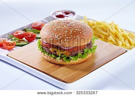 Juicy Tasty Hamburger On A Wooden Cutting Board With French Fried Fries, Vegetables And Ketchup. Iso