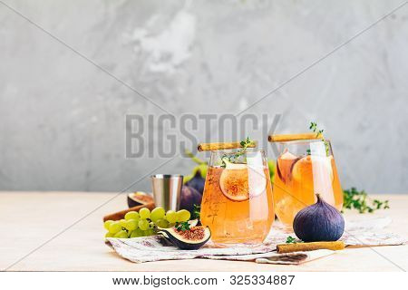 Pink Cocktail With Fig, Thyme, Cinnamon And Grapes In Glass On Pink Concrete Background, Close Up. A