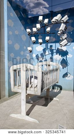 Banksy Baby Mobile On Display In A Shop Window In Croydon, London. Part Of A Public Art Show. The Mo