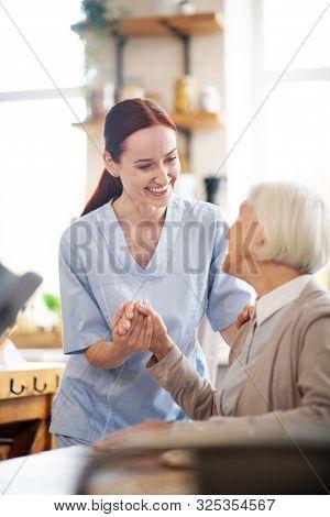 Caregiver Enjoying Work While Communicating With Pensioner