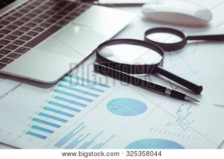 A Desk, White Table With A Computer, A Graph, A Magnifying Glass And A Calculator.