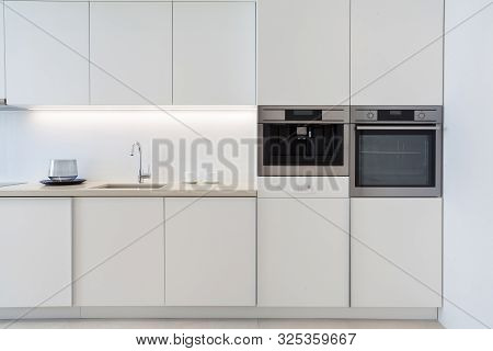 White Modern Apartment With Contemporary Interior At Kitchen. New Household Appliance, Sink With Chr