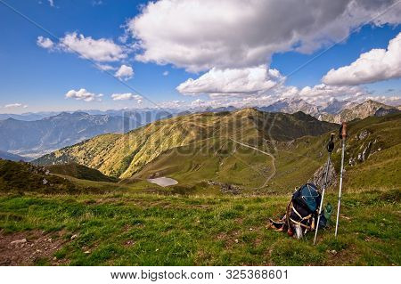 Mountain Landscape. Backpack And Mountain Sticks. Hiking, Travel And Adventure Conceptual Image.