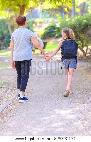 Grandma And Pupil Kid Holding Hands Going To School.little Girl With School Bag Or Satchel Walking T