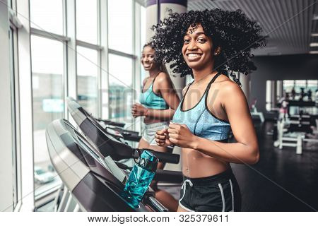 Side View Of Two Beautiful Black Girls On Treadmill In Gym. Two Smiling Women Looking Camera. Weight