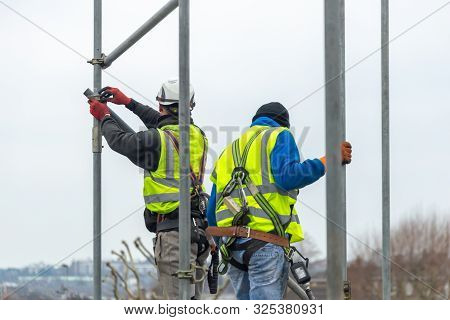 Professional Scaffolders Erecting Scaffolding On A Building In The Uk