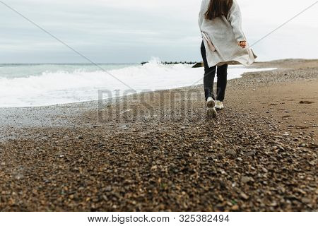 A Beautiful Young Girl Walks Along The Seashore, A Storm, Hair Fly Apart, A Gray Cardigan, A Sports