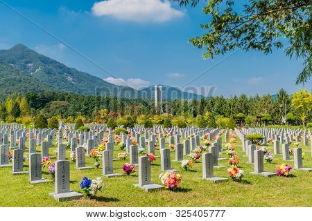 Daejeon, South Korea; September 29, 2019: War Memorial Rising Above Trees With Rows Of Headstones In