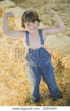 Young boy wearing overalls and flexing muscles in hay