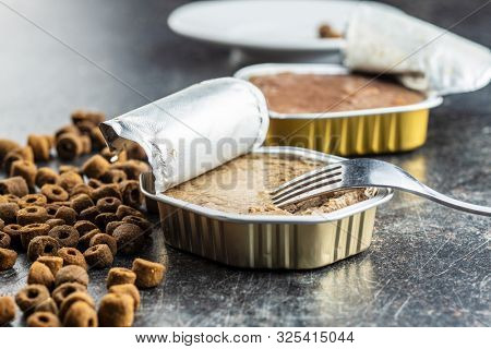 Wet and dry pet food. Cat or dog pate on old table.