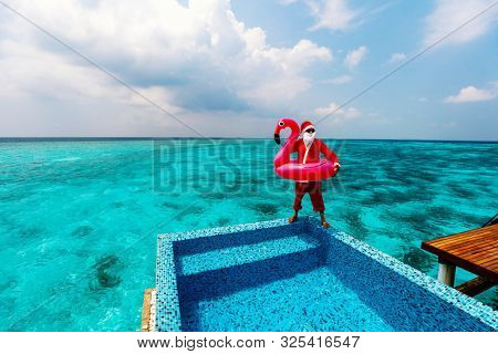 Santa Claus at tropical luxury resort enjoying  Christmas vacation in overwater villa with swimming pool