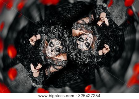 Two scary and beautiful Katrina Calavers looking up at camera over dark background. Fashion model with sugar skull makeup. Dia de los muertos. Day of The Dead. Halloween.