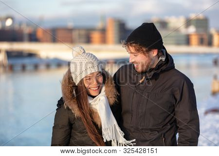 Happy winter friends couple laughing together walking in city outdoors wearing cold weather accessories, hats, jackets, scarf. Asian girl taking with Caucasian man outside.