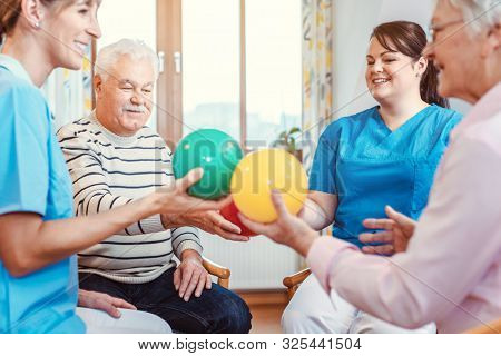 Group of seniors doing sport and gymnastics with balls in the pensioners home