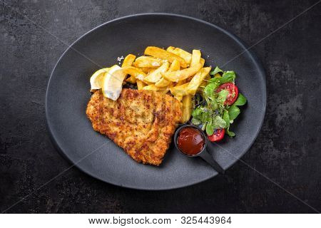 Deep fried Wiener schnitzel from veal topside with French fries and lettuce as top view on a modern design plate