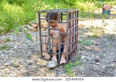 Child slavery. A child through the bars of a steel cage reaches for a bowl of bread with his hand. Child abduction, child abuse concept poster