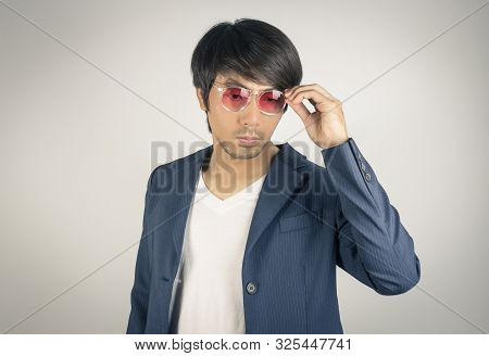 Portrait Asian Casual Businessman In Navy Blue Suit Touching Red Eyeglasses On Grey Background. Casu