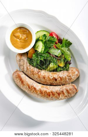 Top view of Munich sausages for frying made from pork and beef with mustard sauce and mixed salad isolated. Traditional German rostbratwurst, wurst or bratwurst with vegetables and greens topview
