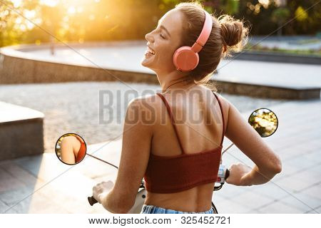 Back view of a beautiful smiling young girl wearing casual summer clothing sitting on a scooter outdoors at the city streets, listening to music with wireless headphones