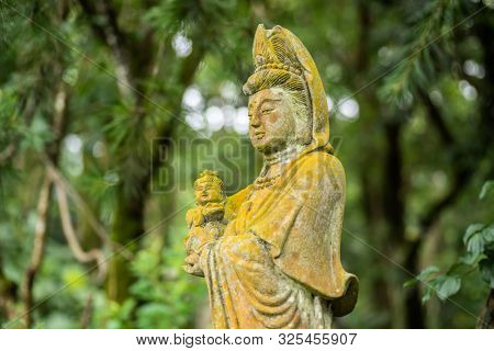 ancient stone bodhisattva statue in a park at outdoor
