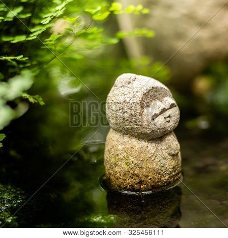 rough stone statue of Earth Store Bodhisattva near a pond