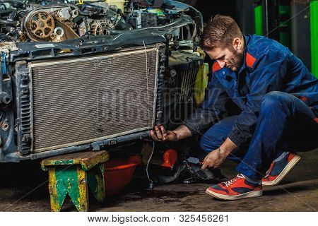 A Tired Mechanic In A Blue Protective Suit Is Repairing A Car Radiator. Repair Service Concept.