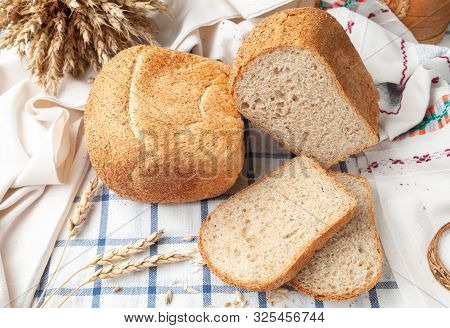 Two Loaves Of Bran Bread. On A White Blue Striped Tablecloth. On The Tablecloth Are Two Sliced ​​pie