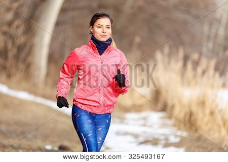 Young Girl On Trail Running Training In Winter