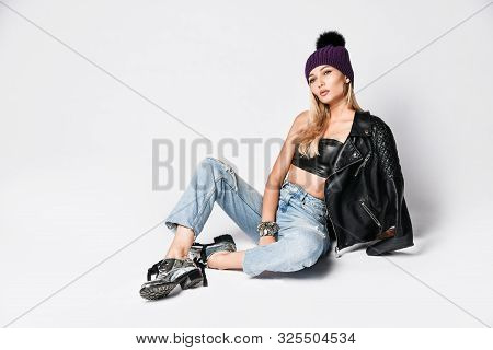 Fashion Art Photo Of Young Grunge Style Blonde Woman In Blue Torn Jeans, Leather Top And Jacket With