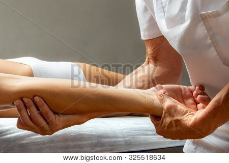 Close Up Of Physiotherapist Doing Curative Manipulation On Forearm Tendon.