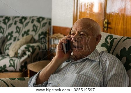 Elderly Man Is Using His Smartphone At Home