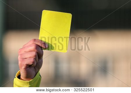 Football Referee Shows A Yellow Card. The Punishment For A Foul.