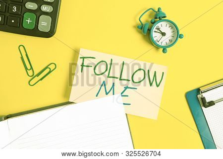 Text sign showing Follow Me. Conceptual photo Inviting a demonstrating or group to obey your prefered leadership Empty orange paper with copy space on the yellow table. poster