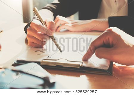 Business Woman Signing A Contract. Close Up Of Two Business Partners Signing A Document For Agreemen