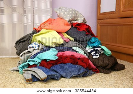 Pile Of Carelessly Scattered Clothes On Floor.
