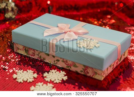 Gift Boxes Lie On A Red Shiny Fabric. Package Of Gifts For Christmas.bokeh, Small Tree, Bright Festi