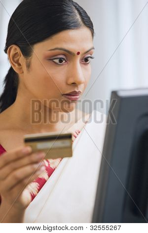 Indian woman in traditional clothing online shopping