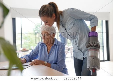 Elderly woman at home with homehelp doing household chores