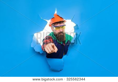Bearded Man In Construction Helmet Through Hole In Paper Pointing At You. Construction Worker In Har