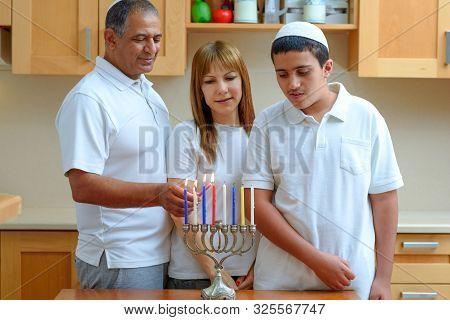Happy Multiracial Jewish Family Is Lighting Candles For The Jewish Holiday Hanukkah. Jewish Dad, Mom