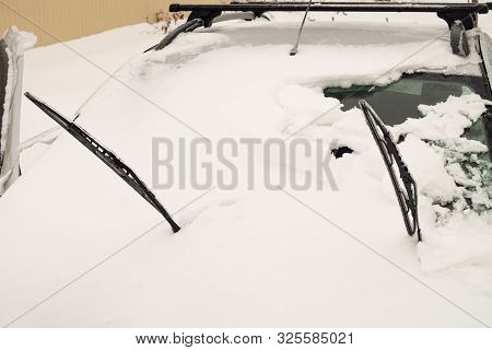 Unprotected outdoor transportation in winter weather conditions. Snowy and icy front part of a car. Ice-covered wipers stick out of the snow. poster