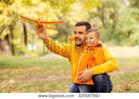 Father And Little Son Play Together In Autumn Park Or Forest. Dad Is Embracing Child And Launching O
